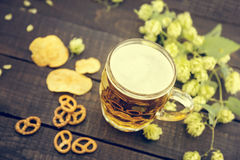 Beer and snacks on black wooden table. Draft cold beer in glass Royalty Free Stock Images