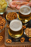 Beer and snacks. On a brown background stock photos