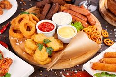 Beer snacks close up. Grilled sausages, nuggets with onion rings and sauces stock images