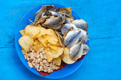 Beer snacks. Close up of the mix beer snacks on wooden background. Potato chips, roasted and salted peanuts, dried fish in blue plate on the blue wood background royalty free stock photo