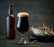 Beer and snacks. Dark beer glass and bottle and salted dried fish snacks stock photography