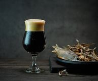 Beer and snacks. Dark beer glass and salted dried fish snacks royalty free stock photography