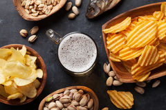 Beer and snacks. Lager beer mug and snacks on stone table. Nuts, chips, dry fish. Top view stock photo