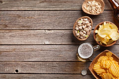 Beer and snacks. Lager beer mug and snacks on wooden table. Nuts, chips. Top view with copyspace stock photos