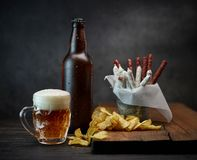 Beer and snacks. Beer mug, bottle and snacks on dark wooden table stock images