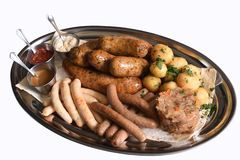 Beer snacks plate. Red, white and yellow sauces on silver dish. Sausage assortment with with young potatoes, fried cabbage on white background isolated on royalty free stock images