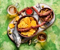 Beer and snacks. Selection of beer and snacks.Chips, fish, beer sausages on the table royalty free stock photo