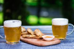 Beer snacks set. Chicken wings on sticks and two mugs of beer. On the cutting board and green summer background royalty free stock image