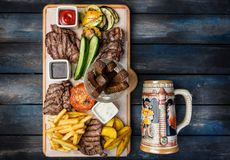 Beer snacks set. Meat set served on cutting board with the antique mug, on the wooden background. stock images
