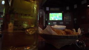 Beer and Snacks Set in Sport Bar with Football Match TV Background. Shot with a Sony a6300 fps29,97 4k stock video footage