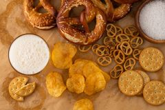 Beer with snacks on stone background. Top view, copy space. Traditional German Savory Lye Pretzel with Salt on Piece of Parchment Paper. Poster Banner for royalty free stock image