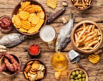 Beer snacks on wooden table. Selection of beer and snacks.Chips, fish, beer sausages on the table stock images
