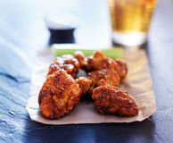 Beer and spicy boneless chicken wings on slate Royalty Free Stock Photos