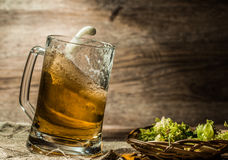 Beer spilling from cup on linen cloth Royalty Free Stock Photography