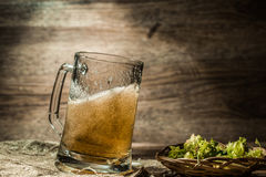 Beer spills from cup on empty wooden background stock photography