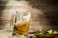 Beer spills from cup on wooden table royalty free stock images