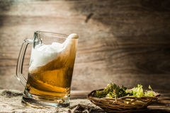 Beer spills from tankard on empty wooden background stock photography