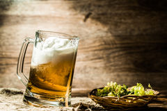 Beer spills from tankard next to hop in basket royalty free stock photography