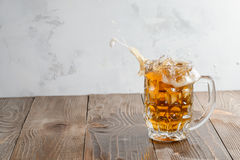 Beer splash in glass on a wooden background royalty free stock photos