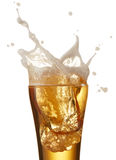 Beer splash. Ice cube dropped into glass of beer creating splash royalty free stock photography