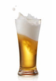 Beer splashing. Glass of splashing beer isolated on white royalty free stock photos