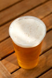 Beer standing on wooden table Royalty Free Stock Image
