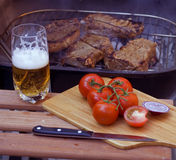Beer and steaks on grill Stock Photography