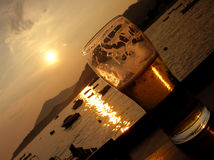 Beer sunset diagonal. Sunset through the glass of cold beer Royalty Free Stock Images