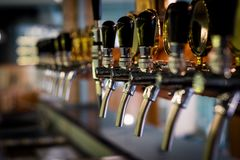 Beer tab on the bar. Row of draft beer tab on the top of counter bar in closeup view, time of celebration, selective focus Royalty Free Stock Photo
