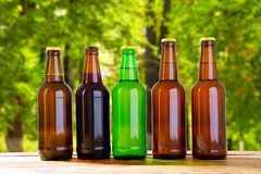 Beer on table on blurred forrest background, summer drinks,coloured bottles.  stock photography