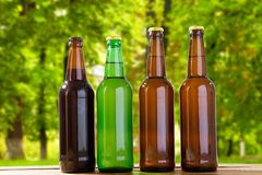 Beer on table on blurred park background, summer drinks,coloured bottles.  royalty free stock photography