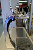 Beer tap with compensator. Chrome faucet with black handles for beer at the bar Royalty Free Stock Images