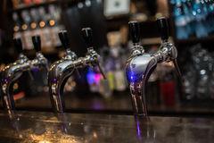 Beer tap. Draught beer tap in a bar. Close up of bar counter with beer tap on foreground Stock Photography