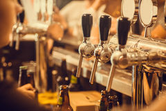 Beer tap with fresh brewed drink in busy pub in Europe.  Royalty Free Stock Images