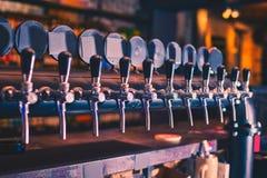 Beer taps in beer bar. Beer tap array stock images