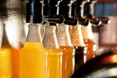 Beer taps beer pouring in bottles. Sorts of beer hanging on beer taps royalty free stock photos