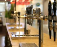 Beer taps on the counter of a pub stock photos