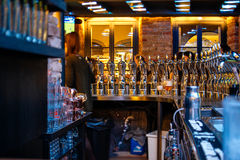 Beer taps inside beer pub bar with silhouette of visitors having royalty free stock photo