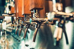 Beer taps in a pub. The beer taps in a pub. nobody. Selective focus. Alcohol concept. Vintage style. Beer craft. Bar table. Steel taps. Shiny taps Stock Image
