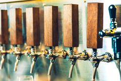 Beer taps in a pub. The beer taps in a pub. nobody. Selective focus. Alcohol concept. Vintage style. Beer craft. Bar table. Steel taps. Shiny taps Royalty Free Stock Photos