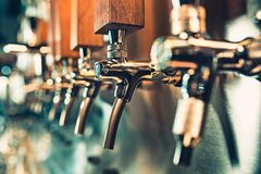 Beer taps in a pub. The beer taps in a pub. nobody. Selective focus. Alcohol concept. Vintage style. Beer craft. Bar table. Steel taps. Shiny taps Royalty Free Stock Image