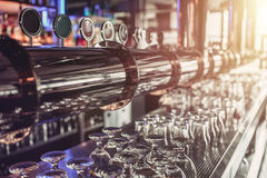 Beer taps in pub. Shiny silver beer taps in pub Royalty Free Stock Images
