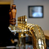 Beer taps. Row of shining beer taps with wooden handles Stock Image
