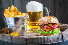 Beer and tasty burger with vegetables, beef and pepperoni Stock Photos