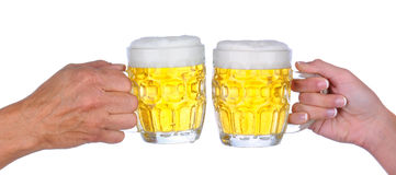 Beer Toast. Closeup of a male and female hand a woman hand holding a beer mug  with a frothy head about to clink glasses, over a white background Royalty Free Stock Image