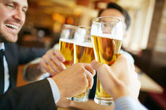 Beer toast. Businessmen drinking beer after successful deal Stock Image