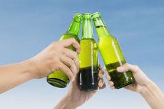 Beer toast. Closeup of hands toasting with bottles of beer Stock Photography
