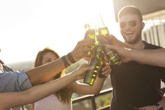 Beer toast. Group of young friends having fun at rooftop party, drinking beer, making a toast and enjoying hot summer days. Selective focus on the beer bottles Royalty Free Stock Photos