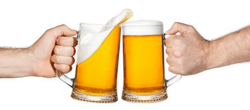 Beer toasting with splash. Hands with mugs of beer toasting creating splash isolated on white background. Pair of beer mugs making toast. Beer up. Male hands Royalty Free Stock Images