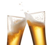 Beer toasting. Two glasses of beer toasting creating splash stock image